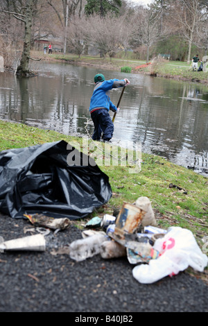 Trash bag with litter gathered from spring park clean-up - Stock Image