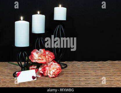 Beautiful orange and white roses, white candle perched on black candle holders on mesh place mat and wooden table with card and dark background. Valen - Stock Image