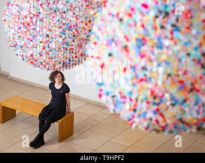 A visitor views 'As I Live and Breathe' - an installation composed of thousands of fragments of colourful waste polythene torn by hand from used shopping bags by artist Claire Morgan - at the Horniman Museum and Gardens, London, part of a series of specially commissioned works drawing on the theme of waste and the impact that humans have on their surroundings. - Stock Image