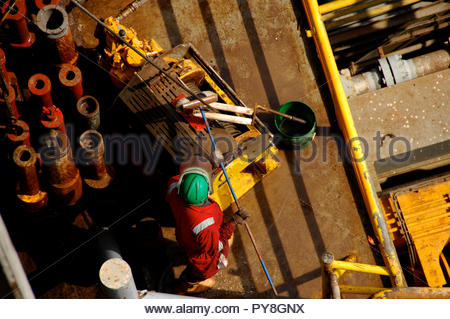 View directly above worker cleaning offshore oil platform - Stock Image