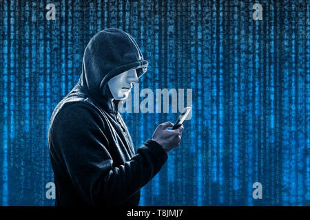 Hooded hacker with mask holding smartphone - Stock Image