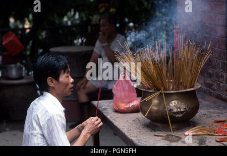 Chinese man ancestral worshipping with incense in a temple in Hong Kong - Stock Image