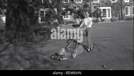 1950s, Elegant lady wearing slacks with new lawn motor outside in her large garden, England, UK. - Stock Image