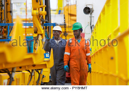 Workers talking by machinery on offshore oil platform - Stock Image
