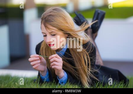 Pretty mesmerizing teenager girl thinker lying on stomach on greenfield - Stock Image