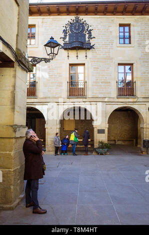 Laguardia, Álava province, Basque Country, Spain : A man stands under the chiming clock on the facade of the  townhall at Plaza Mayor square in the hi - Stock Image
