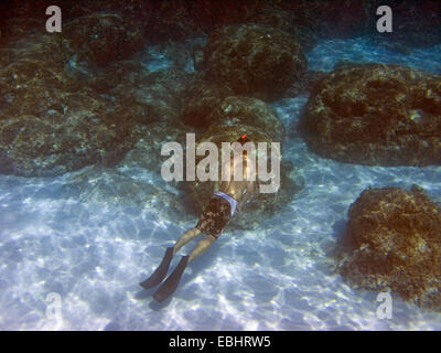 A teenager is snorkling in the Blue Lagoon, near Cape Greco, Cyprus, Europe. - Stock Image