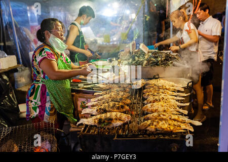 CHIANG MAI, THAILAND - AUGUST 27: Food vendor cooks fish at the Saturday Night Market (Walking Street) on August 27, 2016 in Chiang Mai, Thailand. - Stock Image