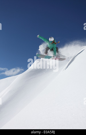 Young woman snowboarding on steep slope, Mayrhofen, Tyrol, Austria - Stock Image