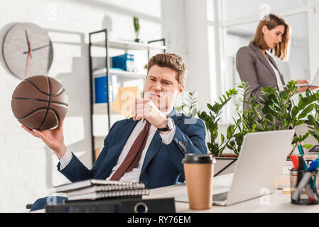 selective focus of dissatisfied businessman looking at sticky notes while holding basketball in office with coworker on background, procrastination co - Stock Image