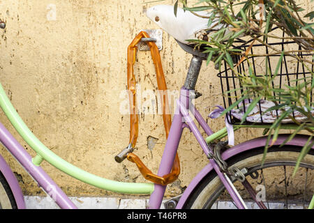 A woman's bicycle is tied to an iron pole. Near there is the red frame of a construction site. - Stock Image