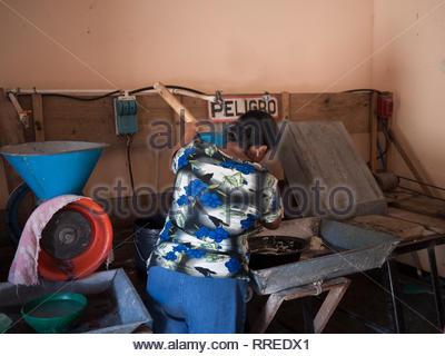 Woman tends a corn mill grinding masa in Jinotega, Nicaragua - Stock Image
