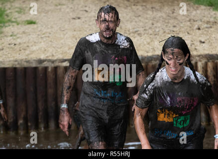 A mud covered couple during an obstacle course run - Stock Image