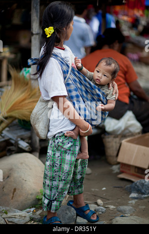 A Hanunoo Mangyan woman shops with her child at a Mangyan market near Mansalay, Oriental Mindoro, Philippines. - Stock Image