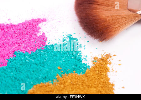 Powdery eyeshadow makeup and brush on a white background - Stock Image