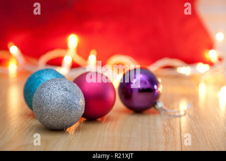 Colored christmas ornaments with white twinkling lights beside a red bag - Stock Image