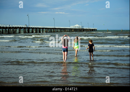 Three children wading in water of Moreton Bay, with historic Shorncliffe Pier in background. Brisbane, Queensland - Stock Image