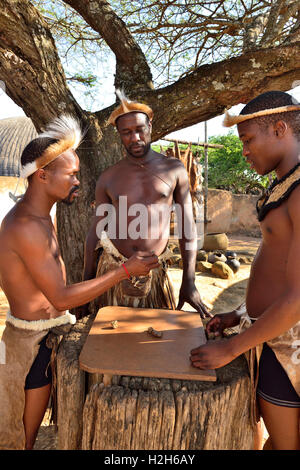 Shakaland Zulu male troupe members in traditional clothes playing  Mancala -The African Stone Game ,Shakaland Cultural - Stock Image