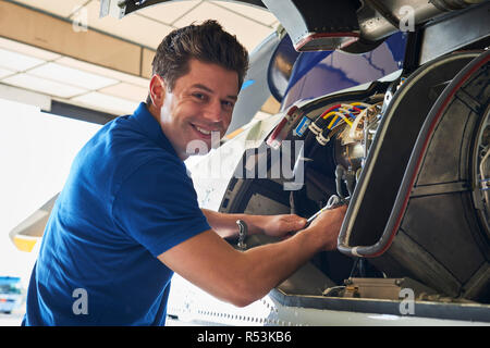 Portrait Of Male Aero Engineer Working On Helicopter In Hangar - Stock Image