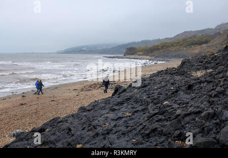 Walking on the famous Jurassic coast beach between Charmouth and Lyme Regis in West Dorset UK - Stock Image