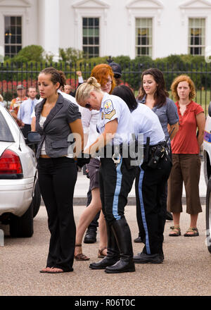 Female environmental activists and protesters arrested for civil disobedience in front of White House (woman arrested, detained) - Washington, DC USA - Stock Image