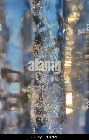 Close up of a row of icicles glittering in the light of the golden winter sun. - Stock Image