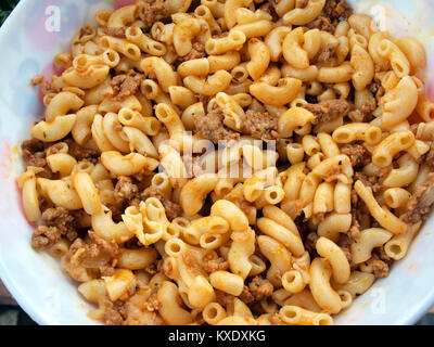 Boiled pasta horns with chopped meat tomato sauce close up - Stock Image