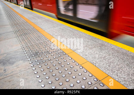 blurred red subway train, diagonal tactile paving also called detectable warning surfaces for visually impaired, yellow line - Stock Image