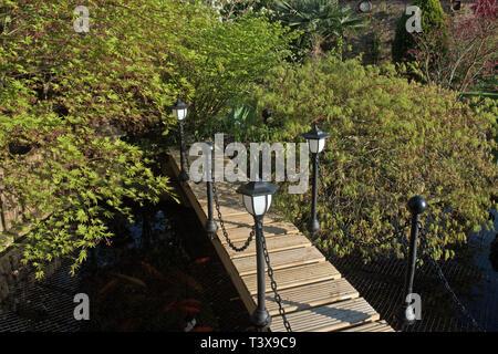 inexpensive wooden footbridge with solar lighting over fish pond - Stock Image