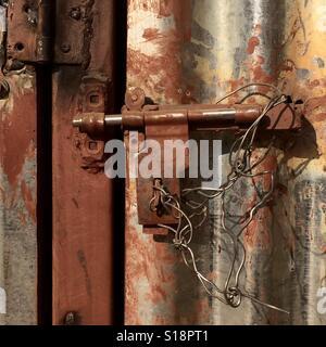 Metal door tied shut with wire - Stock Image