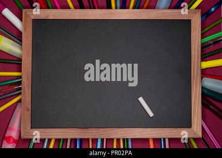 Back to school and education concept. Blackboard with colorful pencils, blank copy space at center - Stock Image