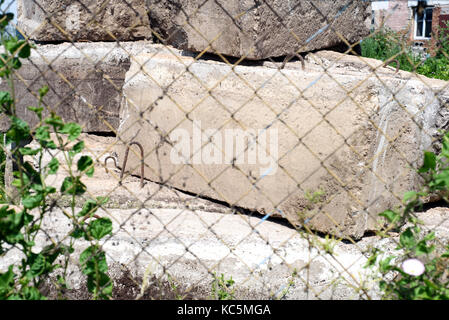 Old concrete blocks used as blockades and in construction seen through a wire mesh fence barricade - Stock Image