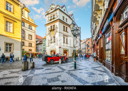 Tourists sightsee, shop and enjoy the cafes as they pass by a vintage red automobile in a picturesque section of Old Town Prague, Czech Republic. - Stock Image