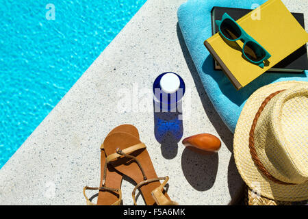 Reading near the swimming pool - Stock Image