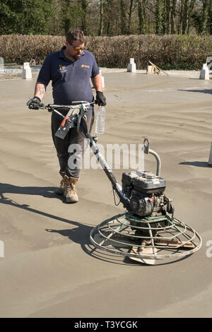 Presteigne, Powys, Wales, UK. A man using a power trowel (power float) to smooth the surface of a freshly laid concrete slab floor - Stock Image