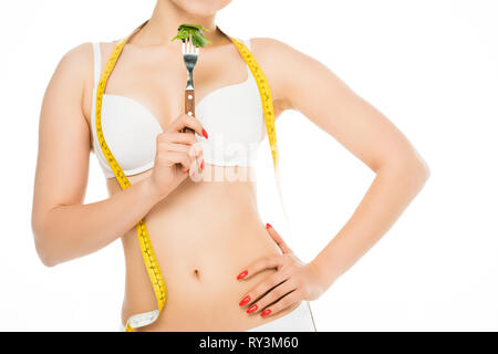 cropped view of slim woman in underwear holding fork with spinach leaves isolated on white - Stock Image