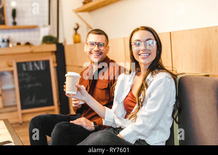 attractive woman holding paper cup and sitting on couch with man in burgundy shirt in coffee house - Stock Image