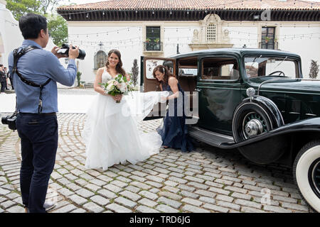 A bride emerges from a vintage 1932 Cadillac & her mother adjusts her wedding dress. At the Vanderbilt Mansion in Centerport, Long Island, New York. - Stock Image