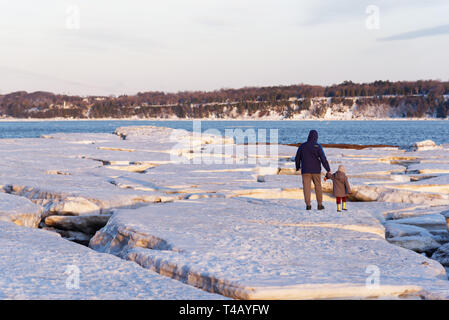 A man and a child walking hand in hand on pack ice on the shore of the St Lawrence at Cap Rouge, Quebec, Canada - Stock Image
