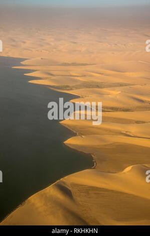 Aerial view of coastline with sandunes of the Namib desert floating in the ocean, Namibia - Stock Image