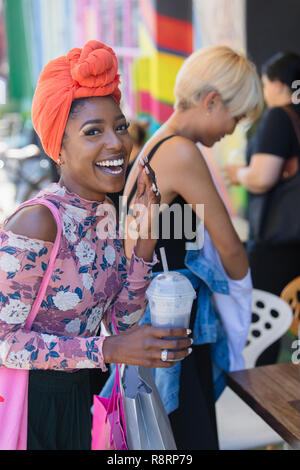 Portrait happy, carefree young woman in headscarf drinking smoothie - Stock Image