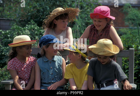 Six young girls in sunhats sitting on bench - Stock Image