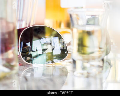 Reflection of an alcoholic drink in sunglasses. - Stock Image