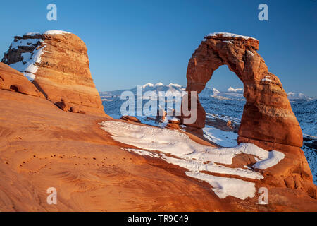 Delicate Arch and La Sal Mountains under snow, Arches National Park, Moab, Utah USA - Stock Image