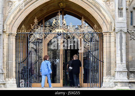 Visitors enter the main door at the west facade of the medieval christian cathedral at Peterborough, England. - Stock Image