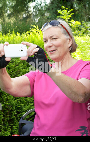 Senior woman outdoors in summer with pink sport shirt, cycling gloves and sunglasses taking a photo with her smartphone, - Stock Image