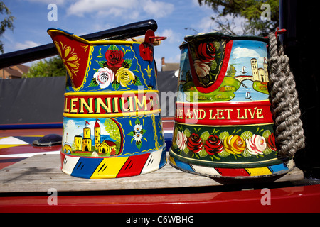 Traditionally decorated water jugs decorated with roses and castles on the roof of working narrowboat, - Stock Image