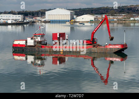 dredger and digger clearing a channel in Portsmouth Harbour - Stock Image