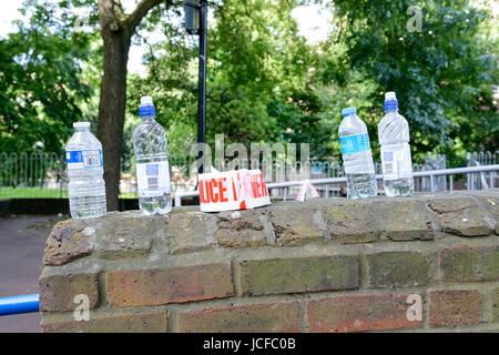 London, UK. 15th June, 2017. Water bottles and police line left near the 24-storey Grenfell Tower one day after - Stock Image