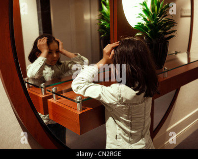 Girl looks at herself in mirror. - Stock Image